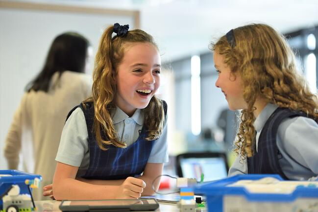 Image of two students using technology to do a practical learning task